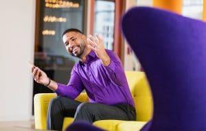 homem-feliz-vestido-com-roupa-social-sentado-em-um-sofa-amarelo