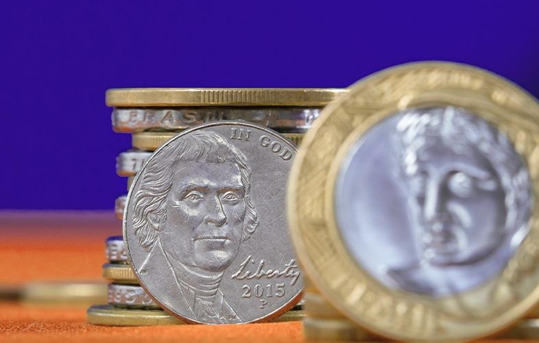 Pilha de moedas brasileiras e uruguaias representando a crise entre Uruguai e Mercosul.