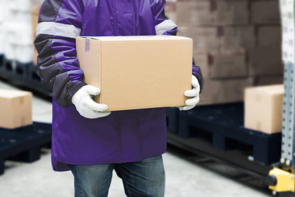 Operador com uniforme roxo e luvas brancas, segurando uma caixa de papelão para fazer a DUIMP.