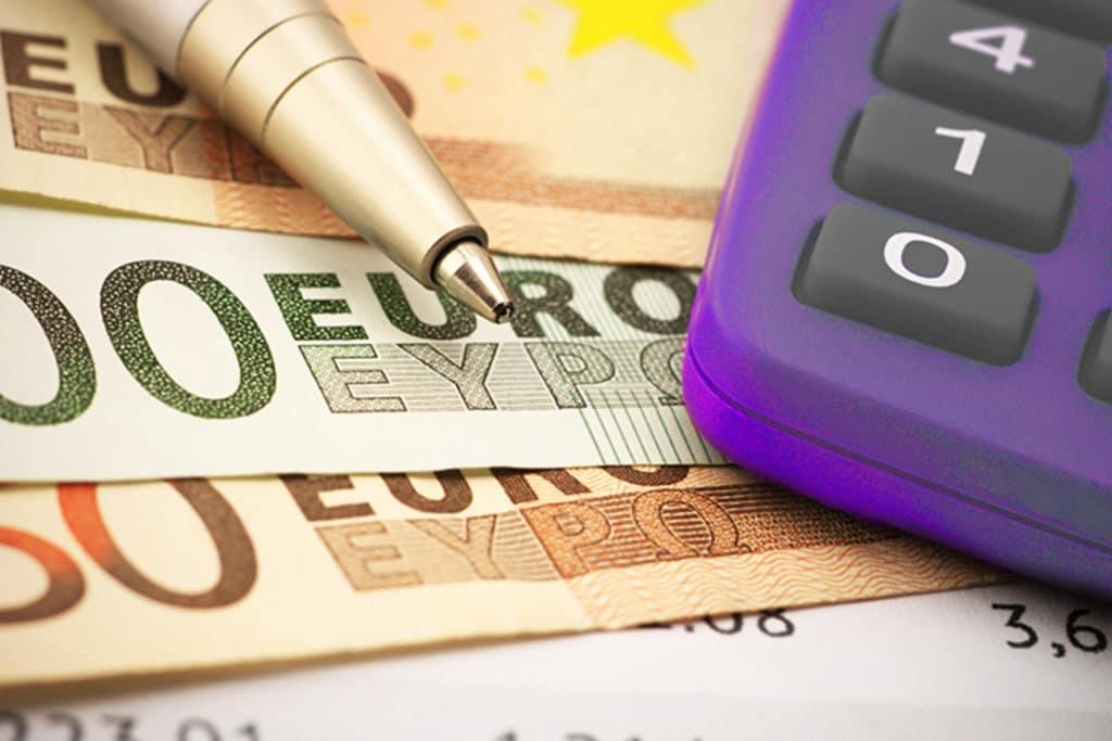 Imagem de uma canela dourada e uma calculadora roxa, em cima de 4 notas de euros, simbolizando o fechamento de câmbio.