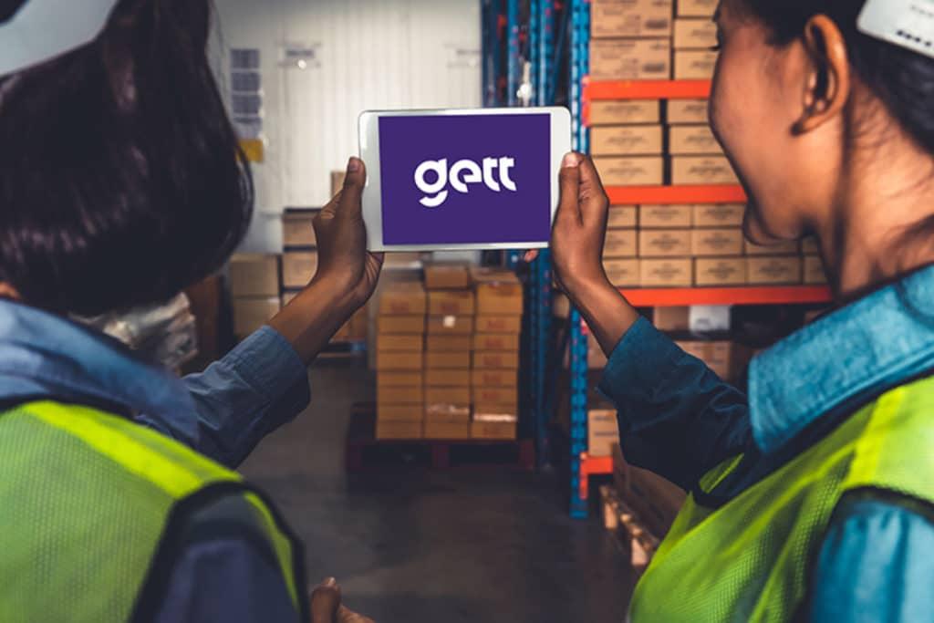 Imagem de duas operárias com seus equipamentos de segurança, segurando um tablet, cada uma com uma mão, que está na tela da Gett Tecnologia. Ao fundo, há um galpão com mercadorias em caixas de papelão.