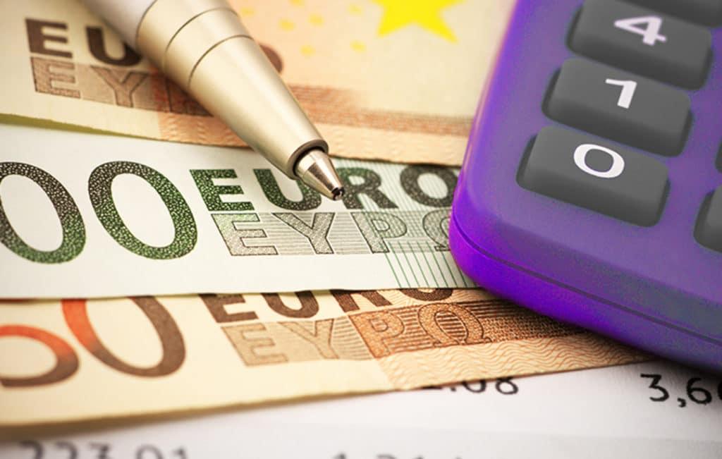 Dinheiro, calculadora e caneta prontos para fazer impostos de importação